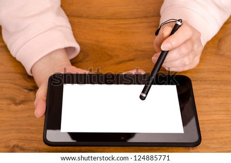 Two female hands with a touch pen on a tablet computer - stock photo
