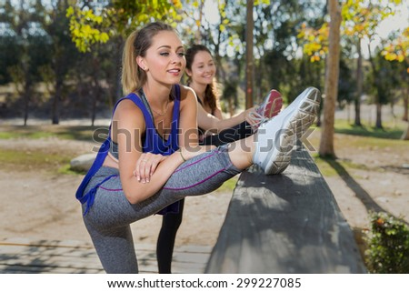 Two female joggers stretching routine warm up before a summer day cardio fitness exercise - stock photo