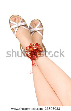 Two female legs in shoes tied up by a red tape with a bow, on a white background, isolated