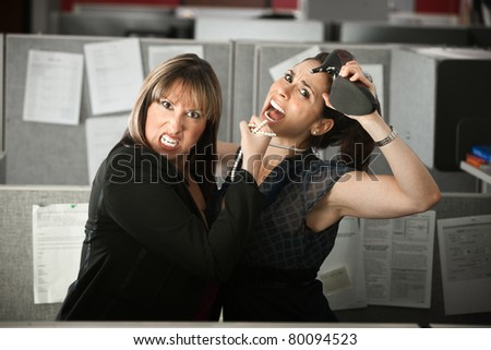 Two female office workers fight in a cubicle - stock photo