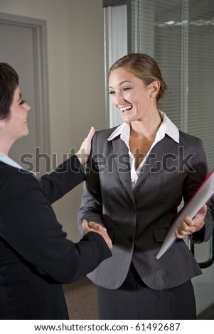 Two female office workers shaking hands at door of boardroom