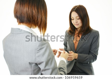 Two female office workers who change a business card each other - stock photo