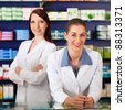 Two female pharmacists standing in pharmacy or drugstore in front of shelves with pharmaceuticals - stock photo