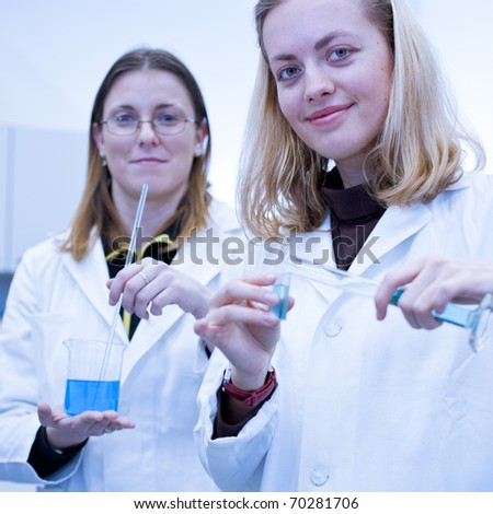 Two female researchers carrying out research in a chemistry/biochemistry lab (color toned image)