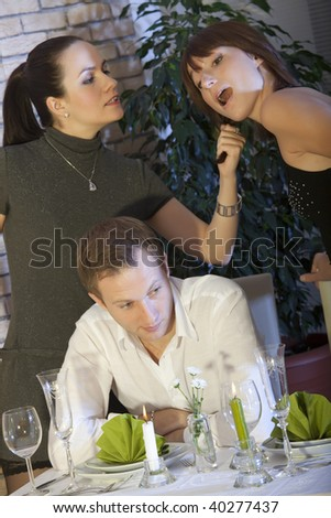 two female rivals fighting over man in a restaurant - stock photo