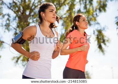 Two female runners working out while listening to music on their mobile phone on an armband - stock photo