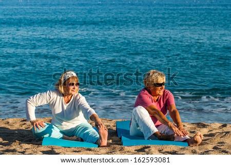 Two female seniors doing health care exercise on beach.  - stock photo