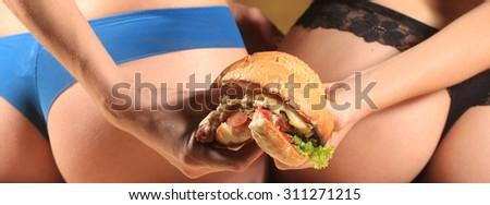 Two female sexy bottoms of ladies in blue and black lace panties holding one big fresh tasty burger of green lettuce meat cutlet cheese onion and white bread bun with sesame seeds, horizontal picture - stock photo