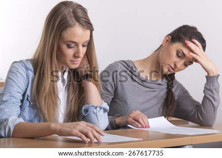 Two female student in the lecture hall learning their stuff