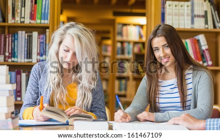 Two female students writing notes at desk in the college library
