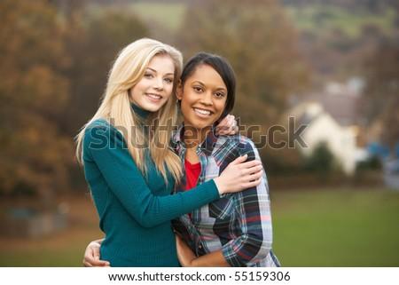 Two Female Teenage Friends On Walk In Autumn Landscape - stock photo