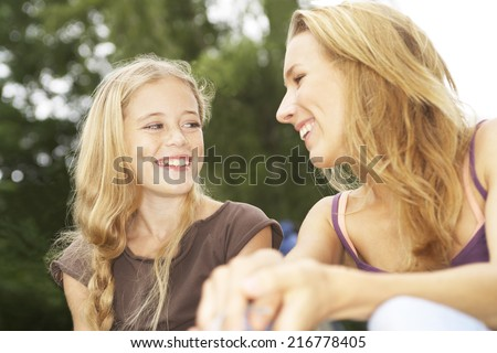 Two female teenagers sitting and laughing.