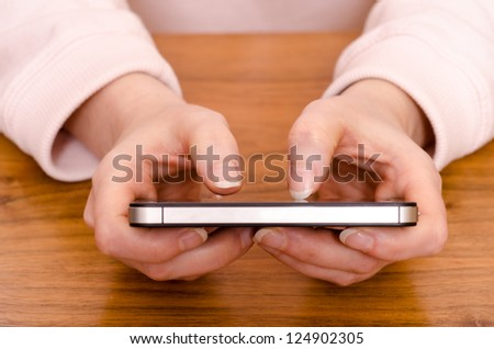Two female thumbs are typing on a smart phone - stock photo