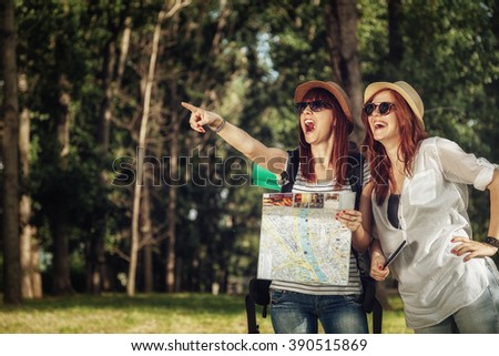 Two Female Tourists In Nature Browsing Map - stock photo
