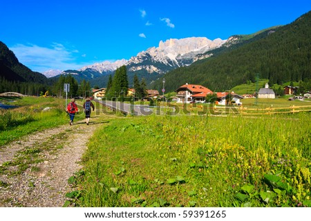 Two female tourists walking scenic path in Dolomite valley. - stock photo
