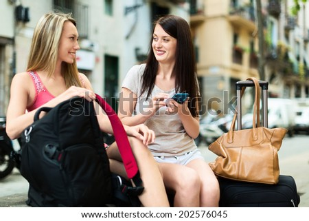 Two female travellers using smartphone navigating system in city. Focus on brunette - stock photo