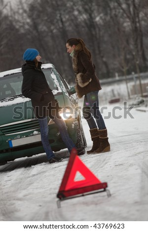 two females and broken car on the road - stock photo