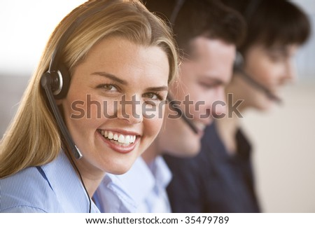 Two females and one male customer service representatives smiling.  They are working on computers and are wearing headsets, and one of the females is looking directly at the camera.