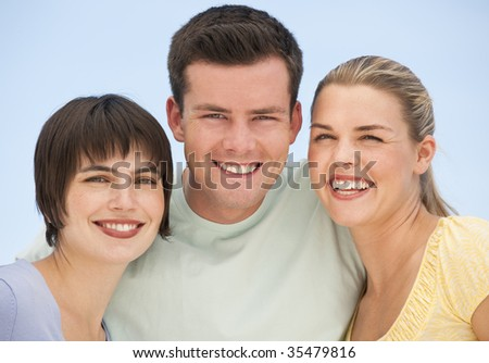 Two females and one male posing for a group photo.  They are smiling.  Horizontally framed shot.