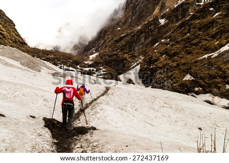 Two females hiking on a snowy trail towards the mountain - stock photo