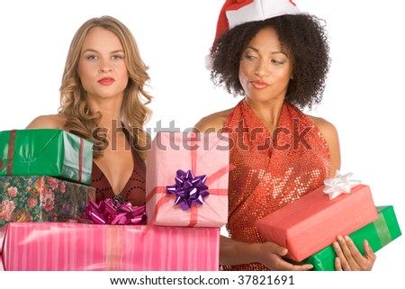 Two females one Caucasian and second ethnic Latina in Mrs. Santa Claus hat with stack of holiday presents. Blond model has much bigger pile and Hispanic lady enviously and disapprovingly looks on it. - stock photo