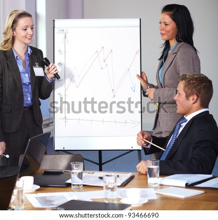 Two females standing and present graph on flipchart during business meeting, have an argue with man sitting at conference table - stock photo
