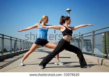 two females stretching on a pier - stock photo