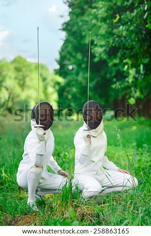 Two fencers women squatting down with rapiers pointing up ready for competition - stock photo