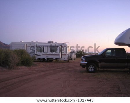 two fifth wheel travelling trailers at sunset - stock photo
