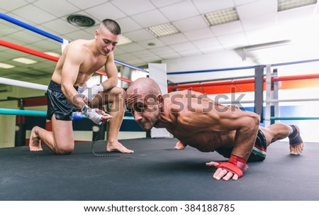 Two fighters training on the ring. Making push ups routines. Concept about sport and fighting - stock photo