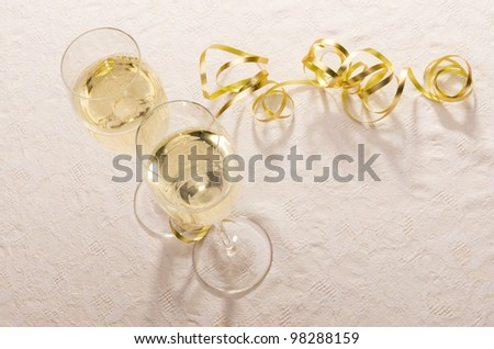 Two filled champagne glasses from above with gold ribbon framing much copy space. - stock photo