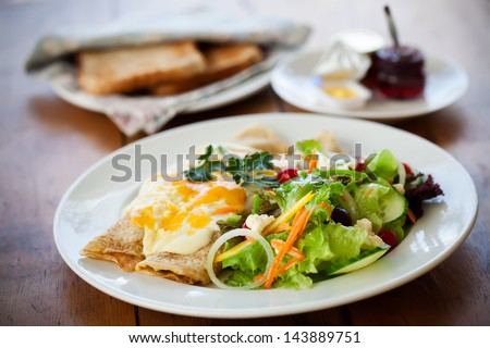 two filled crepes dribbled with cheese sauce plated with a healthy salad and some toast with condiments in the background all on a wooden table