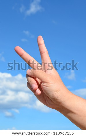 Two finger of human hand on blue sky background - stock photo