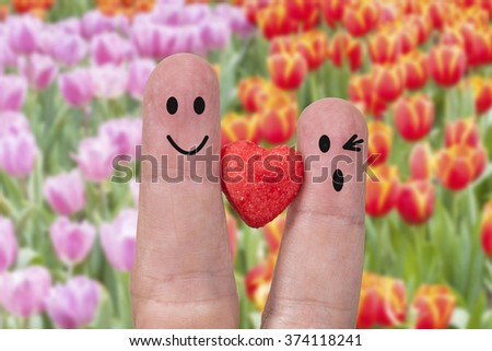two fingers are symbols of love couples,one red heart of 