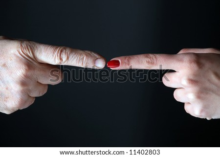 two fingers are touching on the black background - stock photo