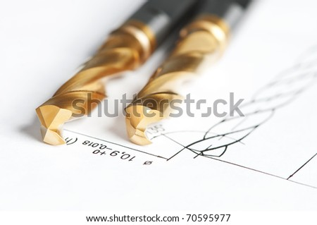 Two finished metal drill tools with protective coating lying on blueprint drawing