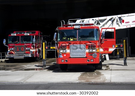 Two fire trucks parked in the bay with all of the fire fighting equipment and gear ready to go - stock photo