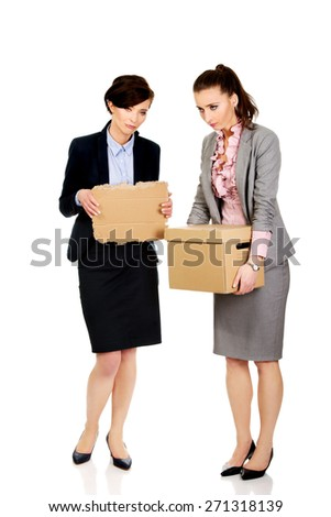 Two fired businesswoman with a box and piece of carton. - stock photo