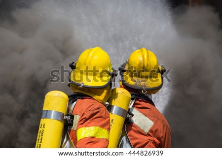 two firefighter in fire fighting suit spray water to fire and black smoke - stock photo