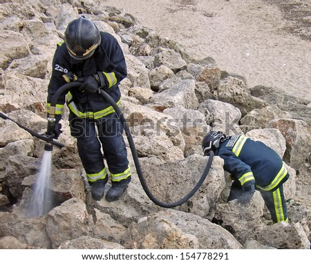 Two firefighters extinguishing a litle fire near a beach in Majorca - stock photo