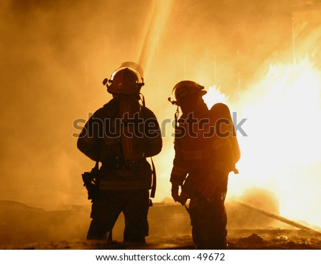 two firefighters hose down a blaze - stock photo