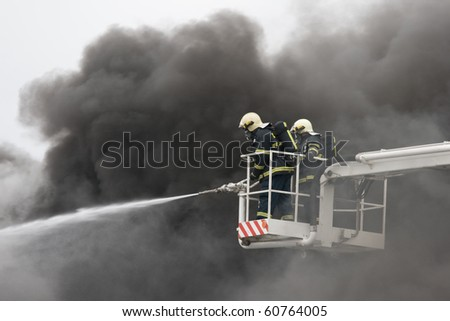 Two firefighters on ramp and smoke in background - stock photo