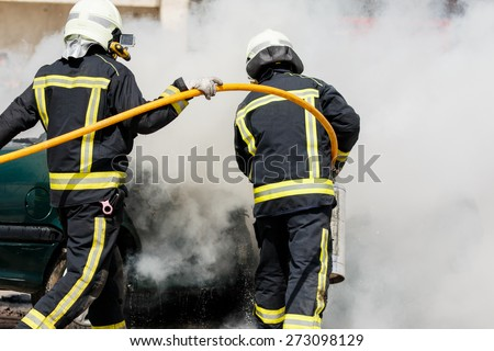 Two firefighters putting out a car fire