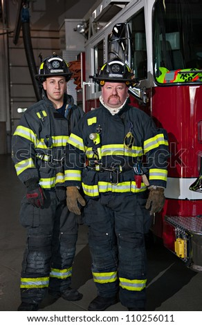 Two Firefighters standing in front fire truck group portrait in fire station