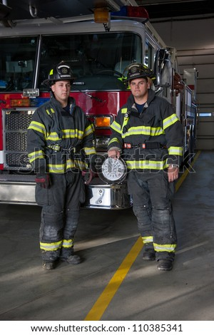 Two Firefighters standing in front fire truck inside fire station - stock photo