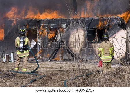 Two firefighters working to put out a fire while a home burns - stock photo