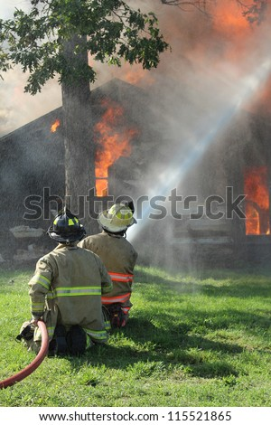 Two firemen direct a high pressure fire hose onto a burning farm house. - stock photo