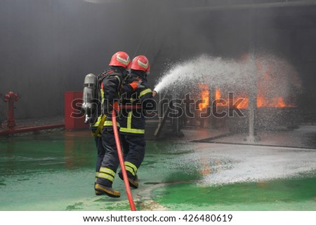 Two firemen fighting the fire - stock photo