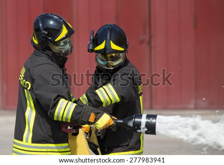 two firemen in action with foam to put out the fire