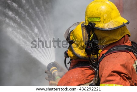two firemen in helmet and oxygen mask spraying water to fire surround with smoke and dust - stock photo